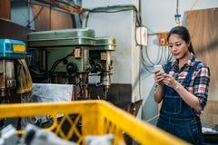 Téléphone portable d'utilisation de personnel féminin d'usine de pièces de jeunes Images stock