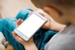 Téléphone portable d'utilisation de petit garçon Blanc, blanc, écran blanc d'isolement d'écran pour la moquerie pour la maquette Photographie stock libre de droits