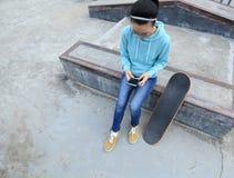 Téléphone portable d'utilisation de planchiste au skatepark Photos libres de droits