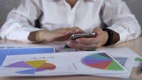 Téléphone portable d'Is Working With de femme d'affaires et diagramme courant Concept économique d'affaires banque de vidéos