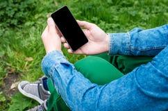 Téléphone portable dans des mains un jeune homme d'affaires de hippie Images stock