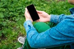 Téléphone portable dans des mains un jeune homme d'affaires de hippie Photos stock