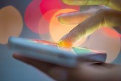 Téléphone portable dans la main d'une femme, ville de fond clair Photos stock