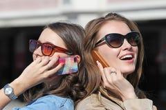 Téléphone portable de deux amis parlant de retour par le dos Images libres de droits