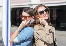 Téléphone portable de deux amis parlant de retour par le dos Image stock