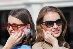 Téléphone portable de deux amis parlant de retour par le dos Photo stock