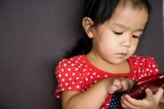 Téléphone portable de jeu de fille avec émotion sérieuse Image libre de droits