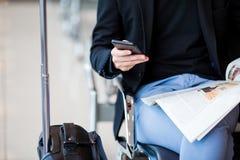 Téléphone portable de plan rapproché dans des mains masculines à l'aéroport tout en attendant l'embarquement Photographie stock