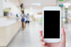 Téléphone portable de prise de main avec l'hôpital brouillé photo stock
