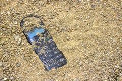 Téléphone portable enterré dans le sable gris photographie stock