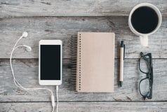 Téléphone portable et écouteur avec une tasse de café sur la table en bois Images stock