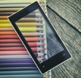 Téléphone portable et crayons Photo stock