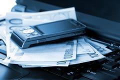 Téléphone portable et euro billets de banque sur l'ordinateur portatif Photos libres de droits