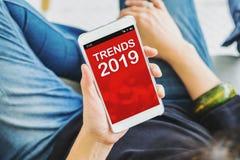 Téléphone portable haut étroit de participation de main de femme avec les tendances 2019 se reposant au café, concept numérique e photo libre de droits