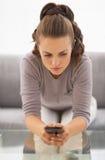 Téléphone portable intéressé de witn de jeune femme dans des mains se reposant sur le divan photos stock