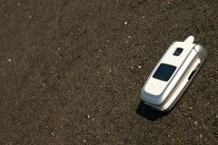 Téléphone portable mobile blanc sur une route photos libres de droits