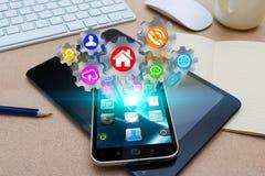 Téléphone portable moderne avec des icônes de roues dentées Photos stock