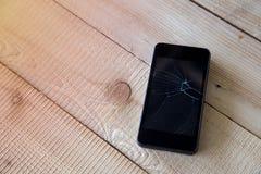Téléphone portable noir cassé sur le fond en bois Photo stock