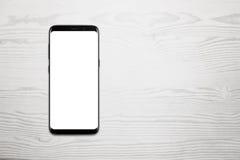 Téléphone portable noir sur le bureau en bois blanc avec l'espace libre pour le texte Image stock