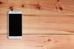 Téléphone portable ou Smartphone avec l'écran vide sur le plancher en bois, vue supérieure images libres de droits