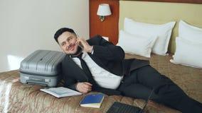 Téléphone portable parlant d'homme d'affaires gai tout en se trouvant sur le lit dans la chambre d'hôtel Voyage, affaires et conc clips vidéos