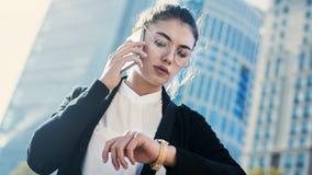 Téléphone portable parlant de femme d'affaires et regarder la montre dans l'extérieur photos libres de droits