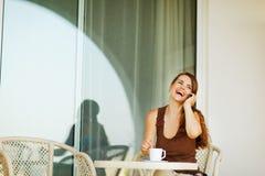 Téléphone portable parlant riant de femme à la terrasse Image stock