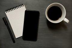 Téléphone portable, protection remarquable quadrillée et tasse de café - sur l'ardoise foncée Photos libres de droits