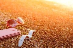Téléphone portable rose, montre-bracelet blanche et verres roses sur Sandy Sea Beach With Waves et la lumière du soleil Téléphone photographie stock