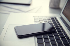 Téléphone portable se reposant sur le clavier d'ordinateur portable Image stock