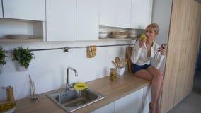 Téléphone portable se tenant femelle de attirance et consommation de la pomme, se reposant sur la surface de cuisine dans la cuis banque de vidéos