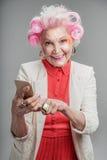 Téléphone portable se tenant femelle supérieur moderne heureux disponible Photo stock