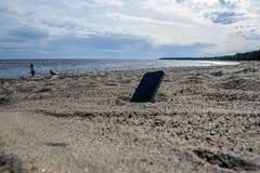 Téléphone portable se trouvant sur la plage dans le sable téléphones imperméables, concept perdu de téléphone, perte de données photos stock