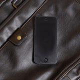 Téléphone portable se trouvant sur un sac en cuir Photographie stock libre de droits
