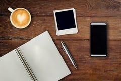 Téléphone portable, stylo de carnet, cadre de photo et tasse de café sur le bureau Photos stock
