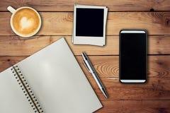 Téléphone portable, stylo de carnet, cadre de photo et tasse de café sur le bureau Photo libre de droits