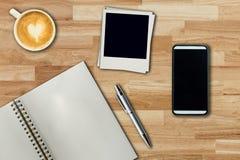 Téléphone portable, stylo de carnet, cadre de photo et tasse de café sur le bureau Image stock