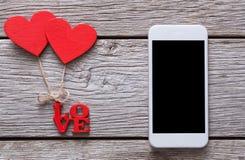 Téléphone portable sur le bois rustique avec des couples des coeurs rouges Image stock