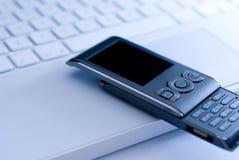 Téléphone portable sur le clavier blanc d'ordinateur portatif Photographie stock libre de droits