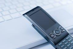 Téléphone portable sur le clavier blanc d'ordinateur portatif Photo stock