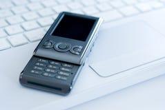 Téléphone portable sur le clavier blanc d'ordinateur portatif Image stock