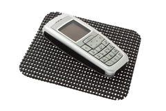 Téléphone portable sur non le couvre-tapis de glissade Image stock