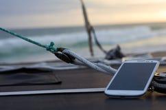 Téléphone portable sur un bateau au coucher du soleil Images libres de droits