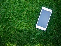 Téléphone portable sur un champ d'herbe artificiel Photo stock