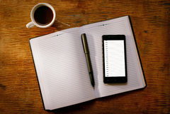 Téléphone portable sur un journal intime ou un journal ouvert Images stock