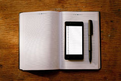 Téléphone portable sur un journal intime ou un journal ouvert Photographie stock