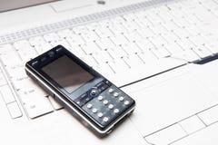 Téléphone portable sur un ordinateur portatif photo stock