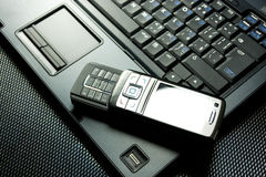Téléphone portable sur un ordinateur portatif Photographie stock libre de droits