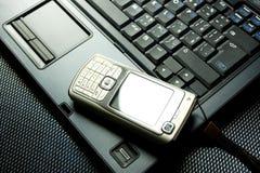 Téléphone portable sur un ordinateur portatif Photos stock