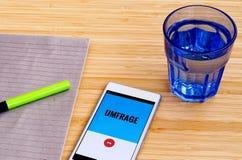 Téléphone portable sur une table en bambou sur la langue allemande photos libres de droits